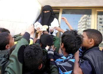 أطفال يمنيون يتجمعون أمام مدرسة للحصول على وجبة غذائية في صنعاء أمس. (رويترز)