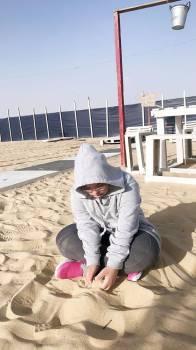 إحدى المستفيدات تمارس اللعب على الرمل.