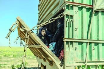 عائلات مقاتلي داعش الذي استسلموا لقوات سورية الديمقراطية، أثناء نقلهم إلى بغداد، أمس الأول (أ.ف.ب.)