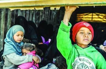 أطفال ونساء على متن شاحنات خلال خروجهم من آخر جيب لـ«داعش» في الباغوز أمس.  (رويترز)