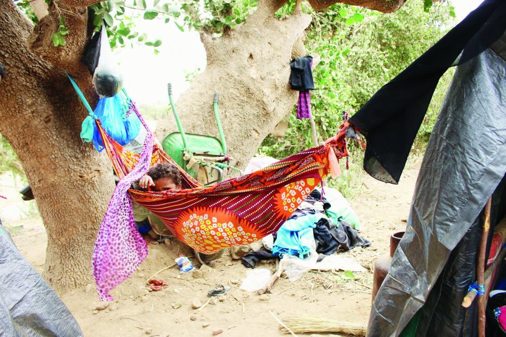 طفل برفقة عائلته في كوخ مؤقت أقامته أسرته تحت شجرة بعد فرارهم من المعارك في كشر بحجة أمس. (رويترز)