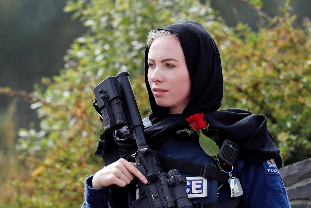 شرطية نيوزلندية ترتدي الحجاب، في مقبرة ميموريال بارك أثناء حضور الناس مراسم دفن أحد ضحايا الهجمات الإرهابية على مسجدين في كرايست شيرش، أمس الأول.  (رويترز)