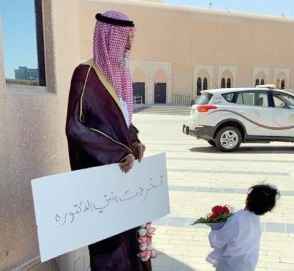 صالح الرشيدي يحمل لافتة لابنته.