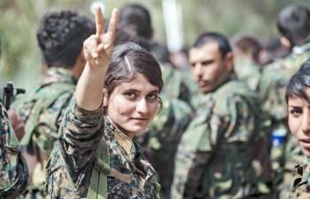 مقاتلة من قوات سورية الديمقراطية ترفع علامة النصر أثناء الاحتفال بهزيمة «داعش» وتحرير الباغوز أمس. (أ ف ب)
