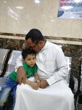 الطفل محمد الناجي من حادثة المعلمات في حضن والده في المستشفى. (عكاظ)