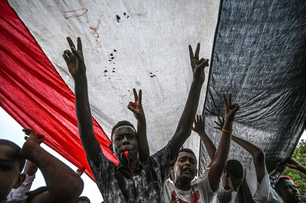 TOPSHOT - Sudanese protesters shout slogans and flash victory signs during a rally outside the army complex in Sudan's capital Khartoum on April 18, 2019. Huge crowds of protesters thronged the Sudanese capital Khartoum today, a week after the army's ouster of president Omar al-Bashir, determined to complete their revolution seeking civilian rule. / AFP / OZAN KOSE