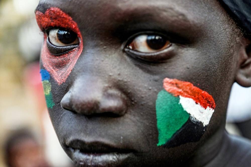 سودانية تتزين بألوان العلم الوطني خلال اعتصام أمام وزارة الدفاع في الخرطوم أمس. (رويترز)