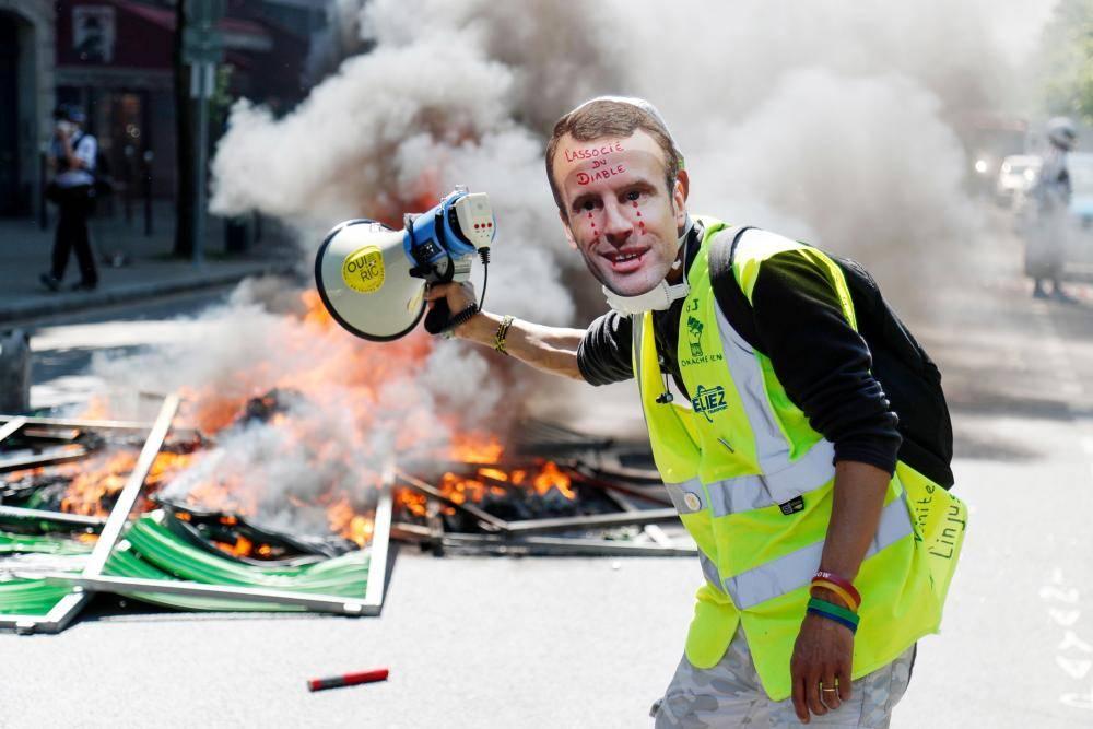 متظاهر يرتدي قناعا لماكرون بجانب حاجز محترق أثناء مظاهرة لمحتجي «السترات الصفراء» في باريس أمس. (أ ف ب)