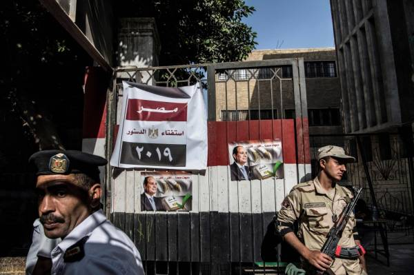 TOPSHOT - An Egyptian soldier and a policeman stands guard a polling station during the third day of a referendum on constitutional amendments in Cairo on April 22, 2019. Egyptians voted for a third and final day Monday on constitutional changes that could keep President Abdel Fattah al-Sisi in power until 2030, amid reports of people actively being encouraged to go the polls. / AFP / Khaled DESOUKI