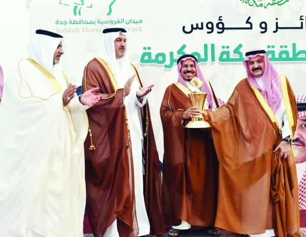 الأمير مشعل بن ماجد مكرما أحد الفائزين في السباق.
