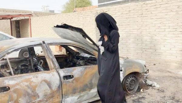 سلمى تقف بجوار سيارتها المحترقة.