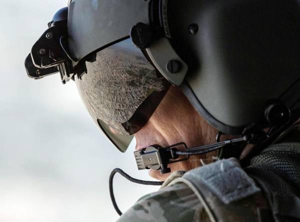 أحد أفراد طاقم مروحية تابعة للجيش الأمريكي أثناء تحليقها بالقرب من مطار بغداد الدولي. (رويترز)
