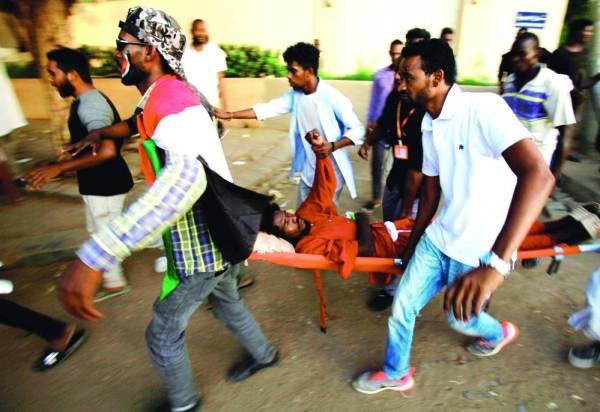 عدد من المتظاهرين يسعفون أحد الجرحى. (رويترز)