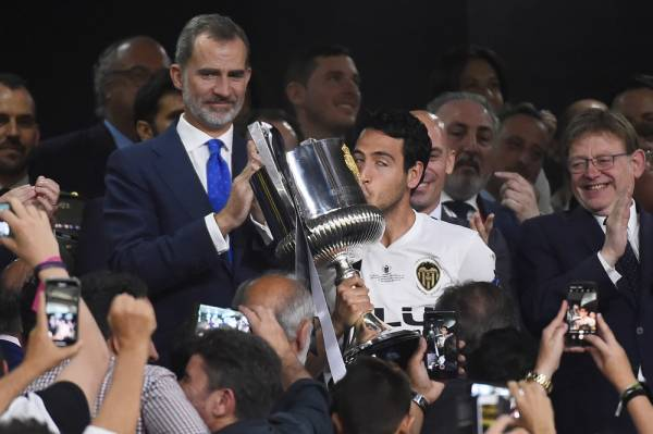 Valencia's Spanish midfielder Daniel Parejo kisses the trophy beside Spanish king Felipe VI after winning the 2019 Spanish Copa del Rey (King's Cup) final football match between Barcelona and Valencia on May 25, 2019 at the Benito Villamarin stadium in Sevilla. Barcelona wanted a trophy to ease their Champions League heartache but instead fell to another shock defeat as Valencia pulled off a thrilling 2-1 victory today to win the Copa del Rey. / AFP / JOSE JORDAN