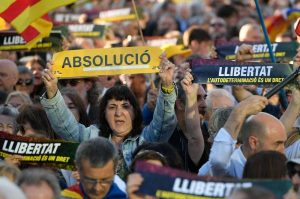 Protesters hold up banners demanding freedom and an acquittal for the 12 Catalan separatist leaders who have been judged in Madrid over their role in Catalonia's failed 2017 independence bid, during a demonstration in Barcelona on June 12, 2019. The four-month trial of Catalan separatist leaders accused of rebellion or disobedience for trying to make their region independent from Spain ended today. / AFP / LLUIS GENE