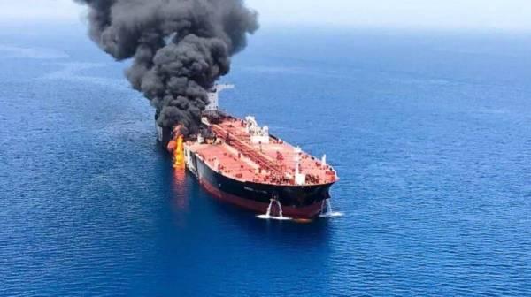 ناقلة نفط يتصاعد منها الدخان عقب هجوم إرهابي تعرضت له في خليج عمان، أمس الأول (أ.ف.ب)