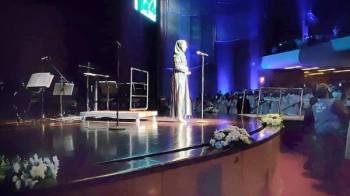 البهيتي على خشبة المسرح مؤدية النشيد الوطني.