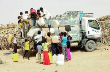 نازحون يمنيون من الحديدة يحصلون على الماء في مخيم بمديرية عبس في حجة أمس الأول. (أ.ف.ب)