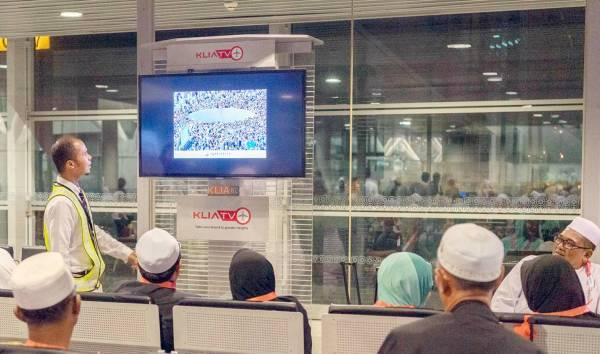 حجاج ماليزيون يتابعون مشاريع الحرمين في مطار كوالالمبور قبيل انطلاقهم إلى مكة.