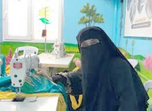السيدة شيخة تعمل على مكينة الخياطة.