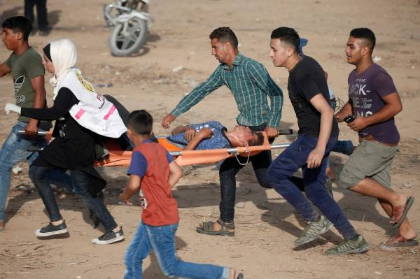 Palestinian paramedics carry away a youth injured during protests along the border with Israel, east of Khan Yunis, in the southern Gaza Strip on July 12, 2019. / AFP / MAHMUD HAMS