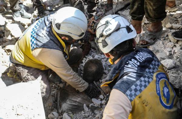 EDITORS NOTE: Graphic content / TOPSHOT - Members of the Syrian Civil Defence (White Helmets) uncover the body of a man killed in a collapsed building following a reported regime air strike on the town of Ariha, in the south of Syria's Idlib province, on July 12, 2019. At least a dozen civilians were killed in Syrian regime air strikes in the country's northwest, including three children, a war monitor said on July 12. / AFP / Omar HAJ KADOUR