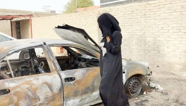 سلمى تقف أمام مركبتها بعد حرقها أمام منزلها قبل نحو عام.