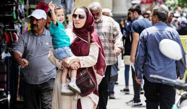 إيرانية تحمل طفلها بأحد شوارع طهران، التي تشهد أزمة اقتصادية وارتفاعا جنونياً في أسعار السلع في ظل العقوبات الدولية المفروضة على النظام.  (أ.ف.ب)