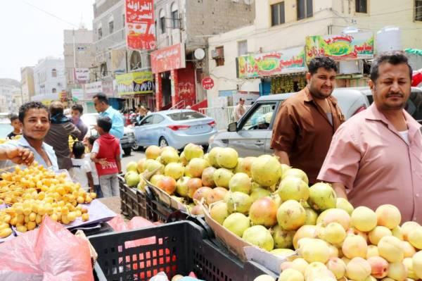 بائع متجول يبيع الفاكهة على عربة تسوق في شارع بمنطقة كريتر وسط عدن، أمس. (أ.ف.ب)