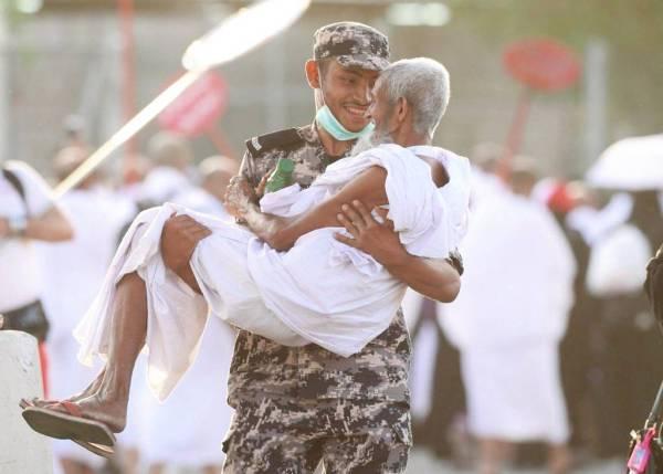 رجل أمن يحمل مسنا. (تصوير: سعود المسيهيج)