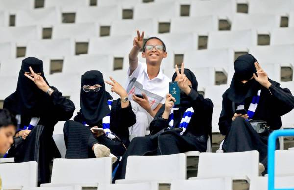 Saudi football fans, including women, flash the victory gesture as they wait for their team in the stands ahead of the AFC Champions League play-off football match between Saudi's al-Ahli and al-Hilal at King Saud University Stadium in the Saudi capital Riyadh on August 13, 2019.   / AFP / -