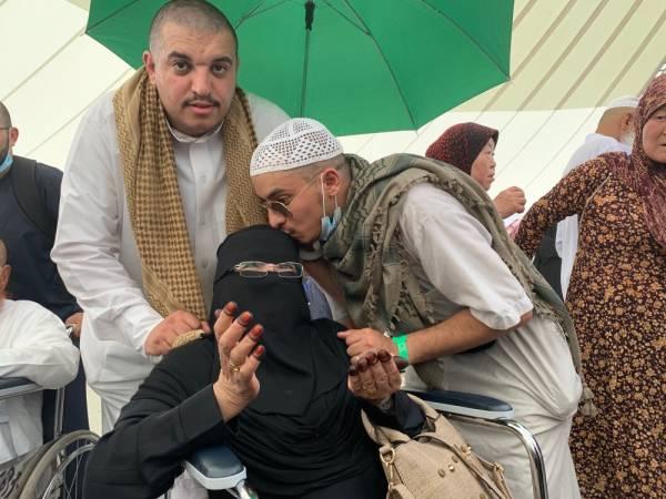 النقيب مهندس جارالله يقبل رأس والداته وبجوارهما أخوه.