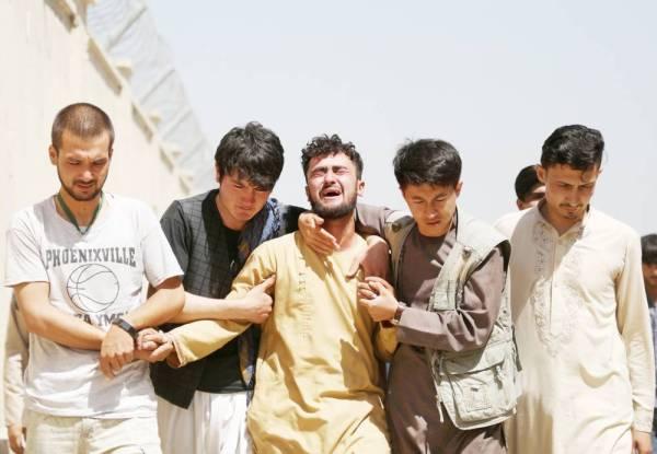 أفغان يبكون خلال تشييع جنازة أقاربهم بعد تفجير انتحاري في حفلة زفاف في كابول أمس. (رويترز)