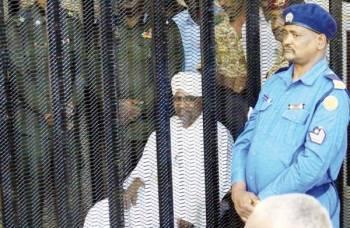 البشير داخل «القفص» يواجه تهما بالفساد خلال بدء محاكمته في الخرطوم أمس. (رويترز)