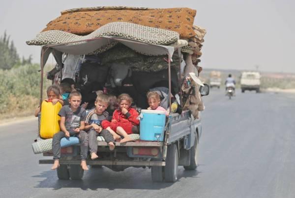 أطفال سوريون يفرون مع أسرهم من مناطق النزاع في إدلب الشمالية الغربية التي يسيطر عليها المتمردون، أمس. (أ.ف.ب)