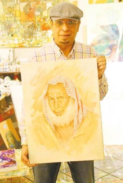 عثمان الخزيم مع إحدى لوحاته.
