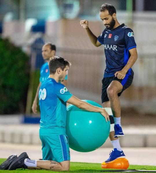 عبدالله عطيف يؤدي تمارين مع مدرب اللياقة بنادي الهلال.