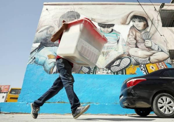 مسؤول في لجنة انتخابية يحمل صندوق اقتراع أمس قبيل ساعات من انطلاق الانتخابات الرئاسية في تونس اليوم (الأحد).  (رويترز)