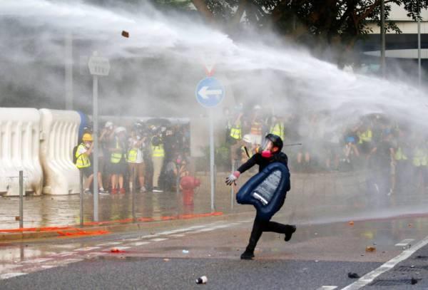 محتج يلقي حجارة على الشرطة خلال مظاهرة قرب مجمع الحكومة المركزية في هونغ كونغ أمس. (رويترز)