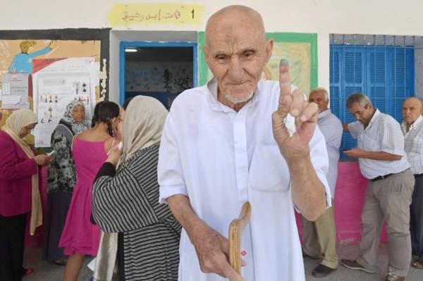 مسن تونسي يرفع إصبعه بالحبر بعد التصويت في مركز اقتراع قرب العاصمة أمس. (أ ف ب)