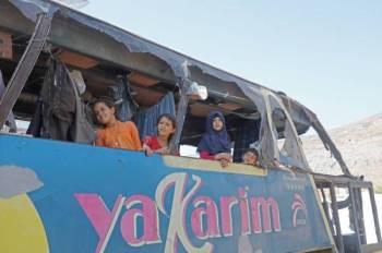 أطفال سوريون نازحون من حماة يلتقطون صورة داخل حافلة مهجورة في إحدى قرى إدلب. (أ ف ب)