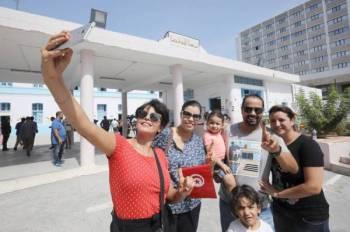 عائلة تونسية تلتقط «سيلفي» عقب التصويت في الانتخابات الرئاسية أمس. (رويترز)