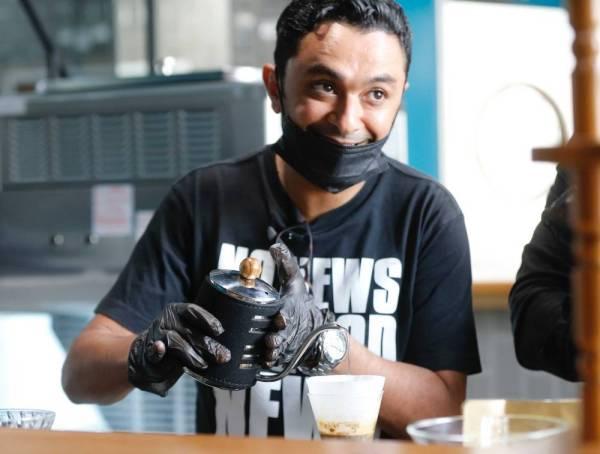 الزميل إبراهيم عقيلي أثناء تدريبه على إعداد القهوة برفقة بعض العاملين في المقهى.