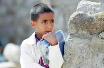 طفل يمني يحمل كتابه وينظر بحزن إلى زملائه الذين يدرسون في الهواء الطلق بعد أن دمر الحوثي مدرستهم في تعز. (أ ف ب)
