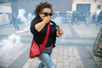 فرنسية تحاول عدم استنشاق الغاز المسيل للدموع خلال مظاهرة لمحتجي «السترات الصفراء» في باريس أمس.  (أ ف ب)