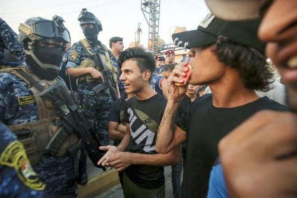 متظاهرون عراقيون يتحدثون مع أفراد من الشرطة في مدينة الصدر أمس الأول. (أ ف ب)