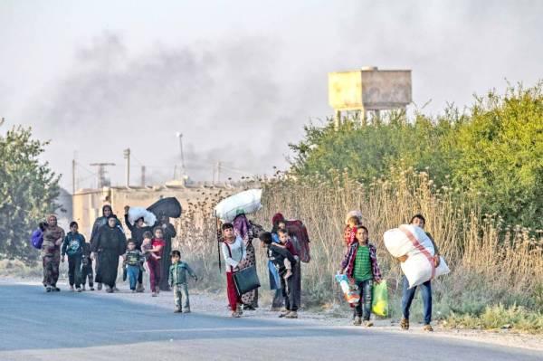نازحون سوريون وقوافل عسكرية تركية في مدينة كيليس بالقرب من الحدود السورية التركية، قبل انطلاق العملية العسكرية بساعات معدودة، أمس. (رويترز)