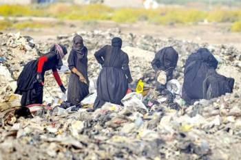 نساء يبحثن في مكبِّ نفايات في الديوانية جنوبي العاصمة العراقية.
