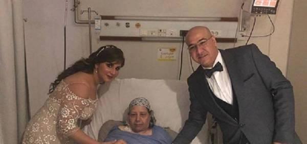 المريضة على السرير الأبيض بجوار نجلها وعروسه.