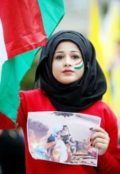 فتاة ترسم علم كردستان على وجهها وتحمل صورة لضحايا العدوان التركي خلال مظاهرة ضد غزو أنقرة للشمال السوري في ستراسبورج أمس. (رويترز)